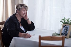 An older woman sits by a bright window with downward gaze